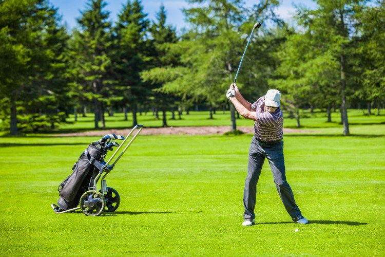 Golfer swinging on the Legacy golf course