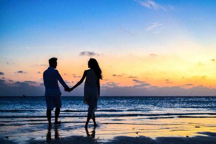 couple walking on beach holding hands at sunset on siesta key near lakewood ranch florida