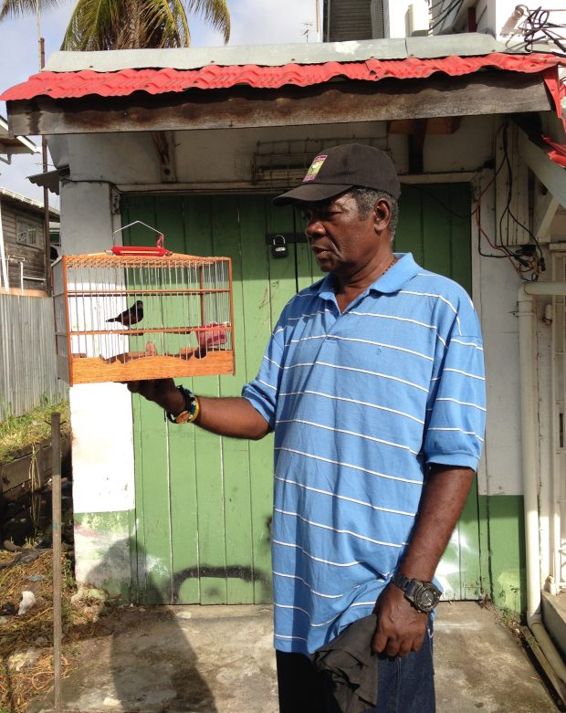 Cecil Bess poses with a bird in front of his house. (Photo by Phillip Pantuso)