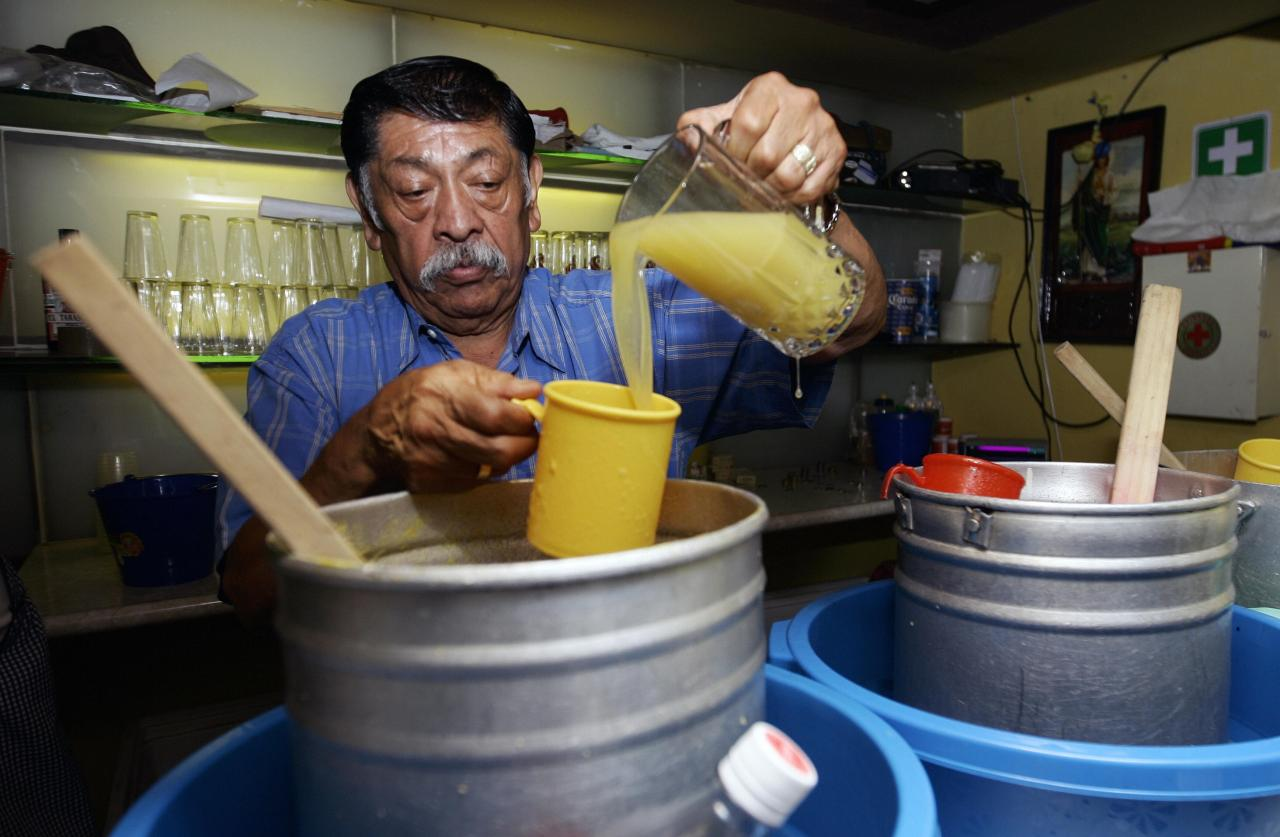 Epifanio Leyva pours pineapple pulque. (Photo by Ronaldo Schemidt/AFP via Getty Images)