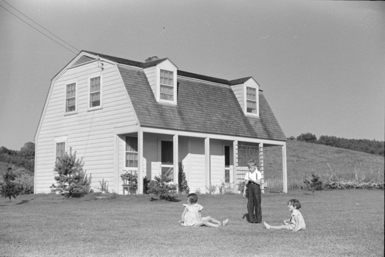 Children of homesteaders play on their front lawn in Tygart Valley, September 1938. As part of the New Deal, the federal government built three homestead communities in West Virginia. The program provided employment opportunities, farmland, and modern, affordable housing for some 25,000 families. Photo by Marion Post Wolcott.