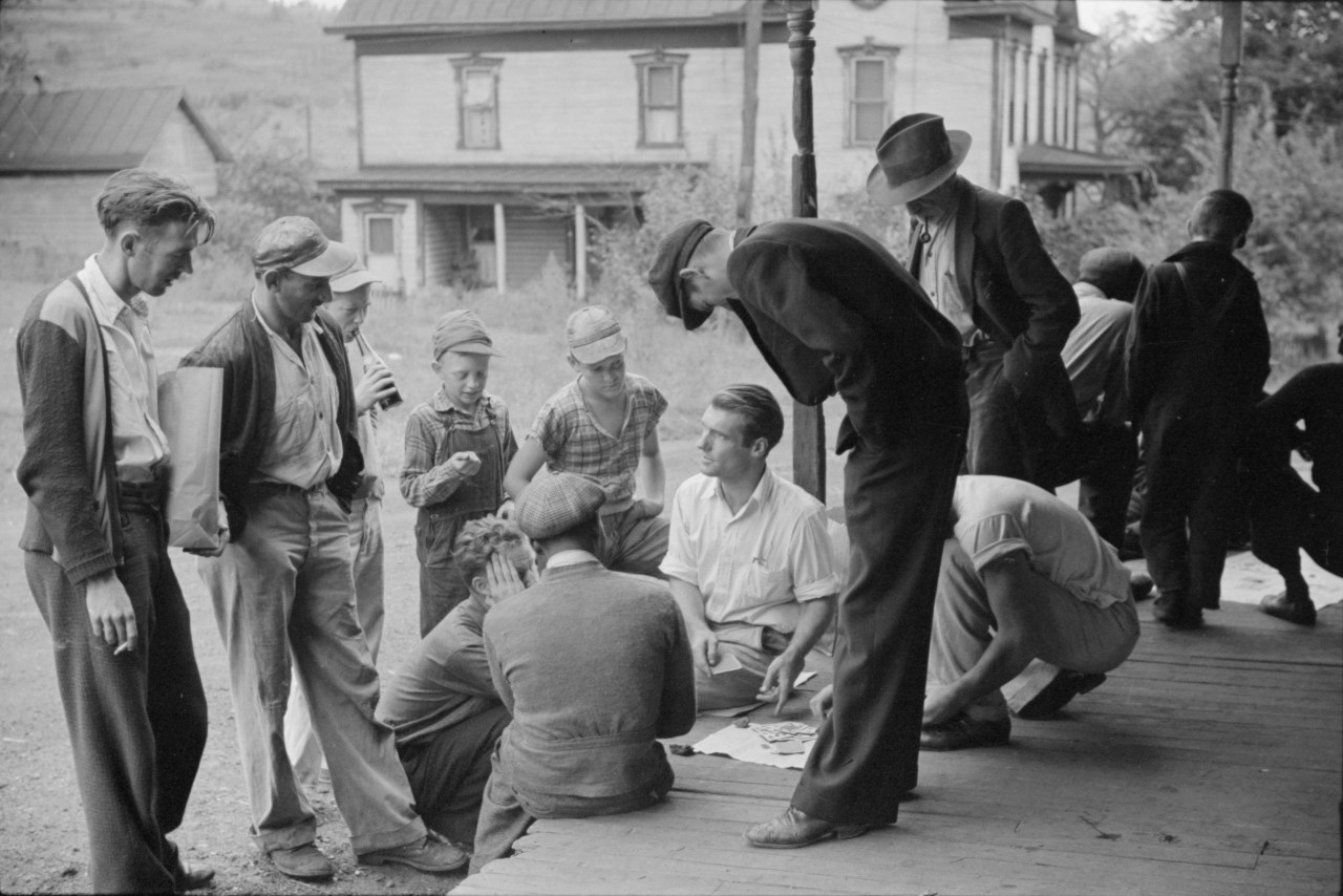 Coal miners gamble on the porch of the company store in Chaplin, September 1938. Photo by Marion Post Wolcott.