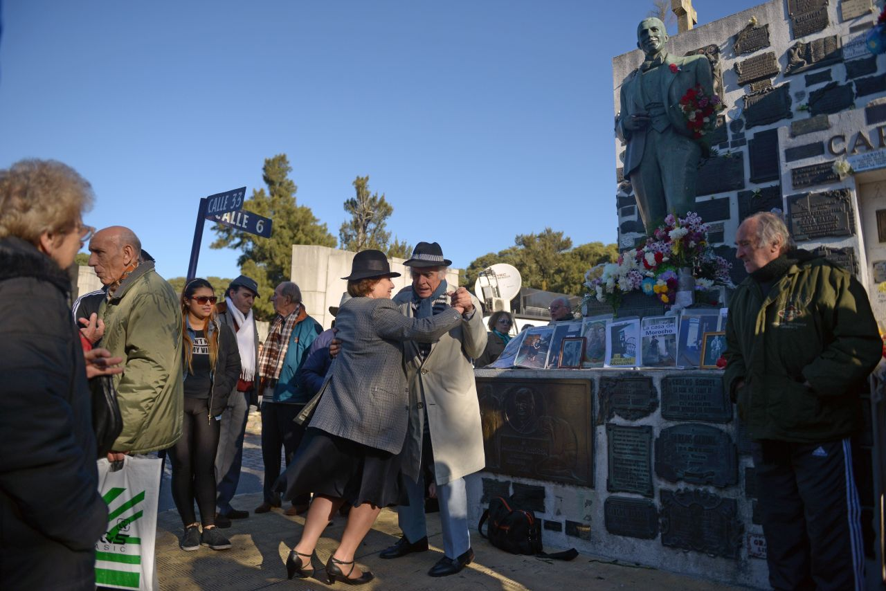 A couple dances by Gardel's grave in Buenos Aires. Photo by EITAN ABRAMOVICH/AFP via Getty Images