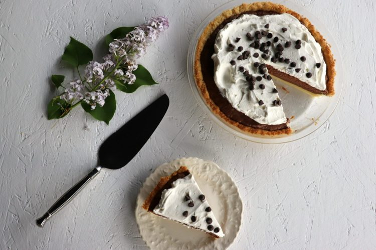 Overhead low carb chocolate pie with piece cut out on a plate, serving piece, lilac