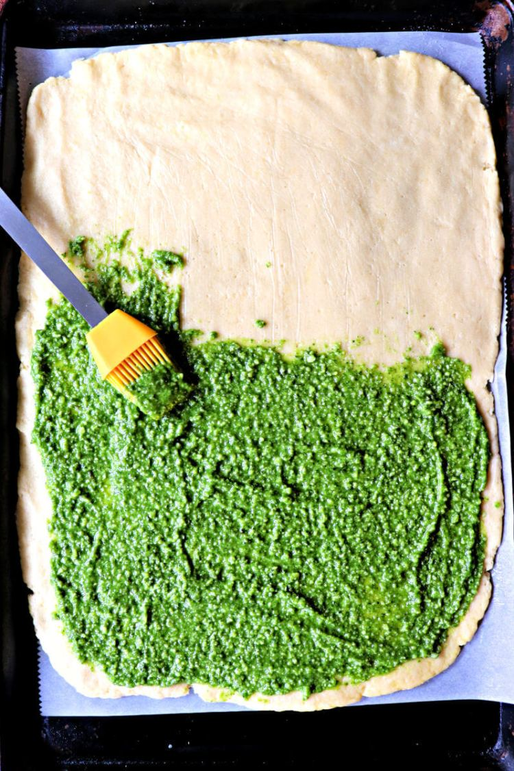 Brushing the pesto on the fathead dough