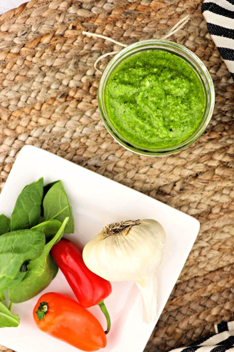 A jar of keto pest with a white plate of garlic, peppers, and spinach #ketorecipes #pesto