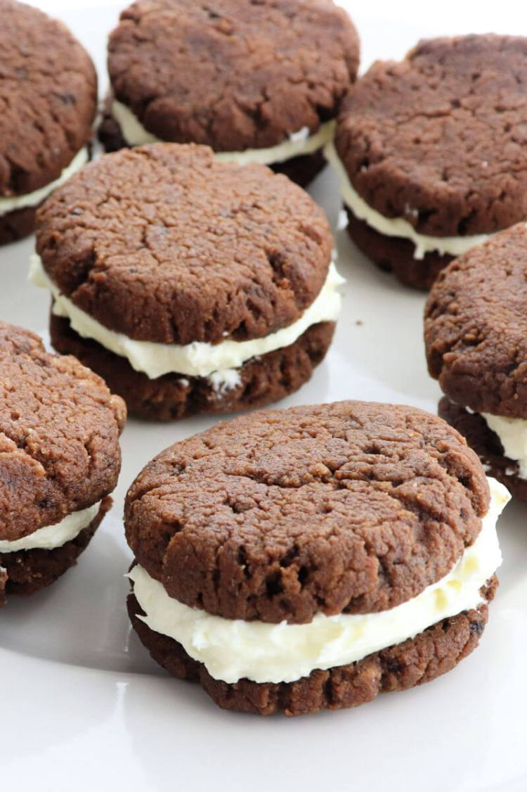Delicious keto chocolate sandwich cookies on a plate are the perfect gluten-free snack. A cross between a keto oreo and a keto whoopie pie, these sugar-free treats are a family favorite. #ketorecipes #lowcarbcookies