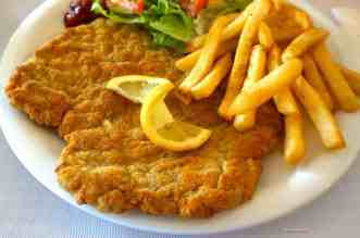 Travel the World Recipes ~ Traditional Schnitzel in Dusseldorf Germany - A plate of food that is on the side of fries - Crispy fried chicken