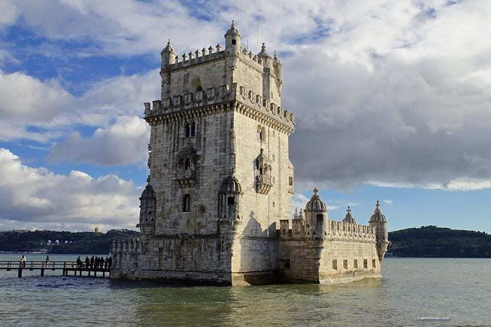 Discovering The Mysteries Of The Belem Tower In Lisbon Portugal - A castle on a cloudy day with Belém Tower in the background - Belém Tower