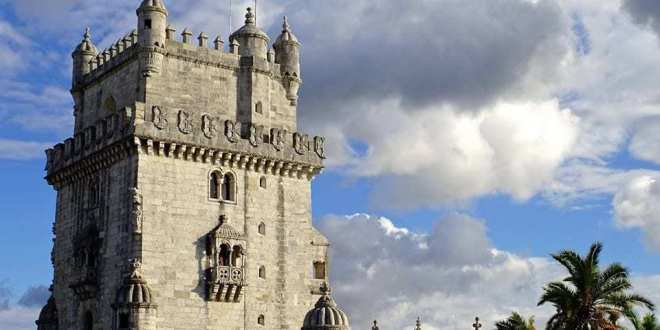 Discovering The Mysteries Of The Belem Tower In Lisbon Portugal - A large clock tower in front of a castle - Belém Tower