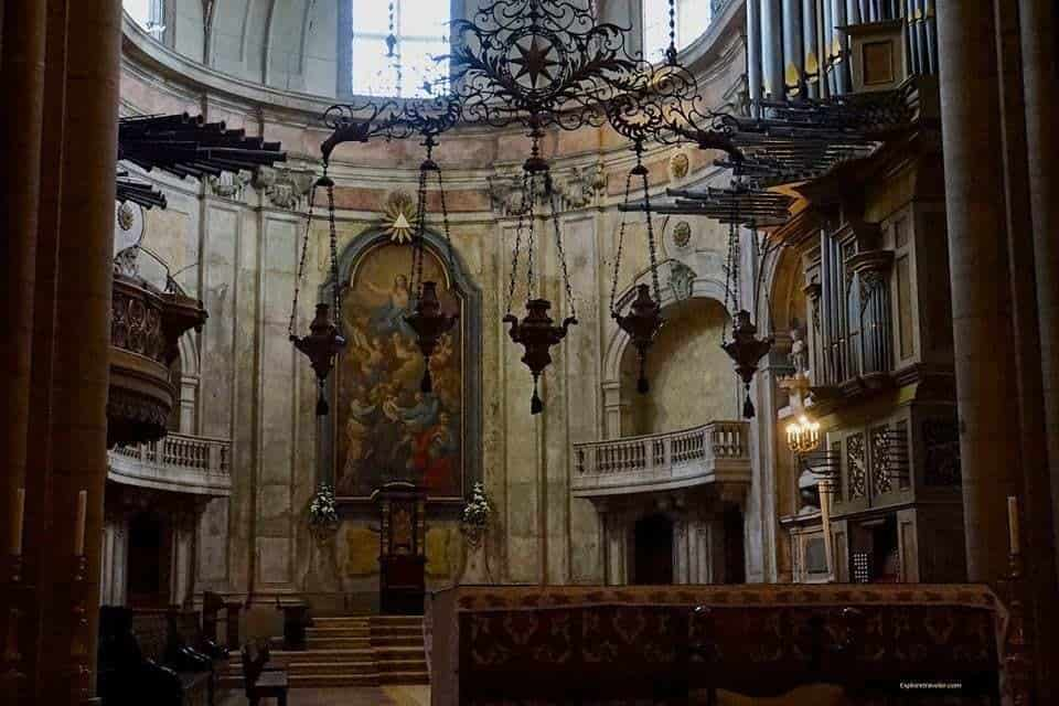 Exploring Sé de Lisboa Cathedral In Lisbon Portugal - A room filled with furniture and a fireplace - Lisbon Cathedral