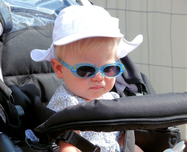 Little girl sitting in a stroller with a hat and sunglasses