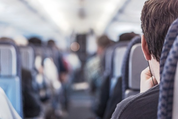 Passenger sitting on a plane with earbuds