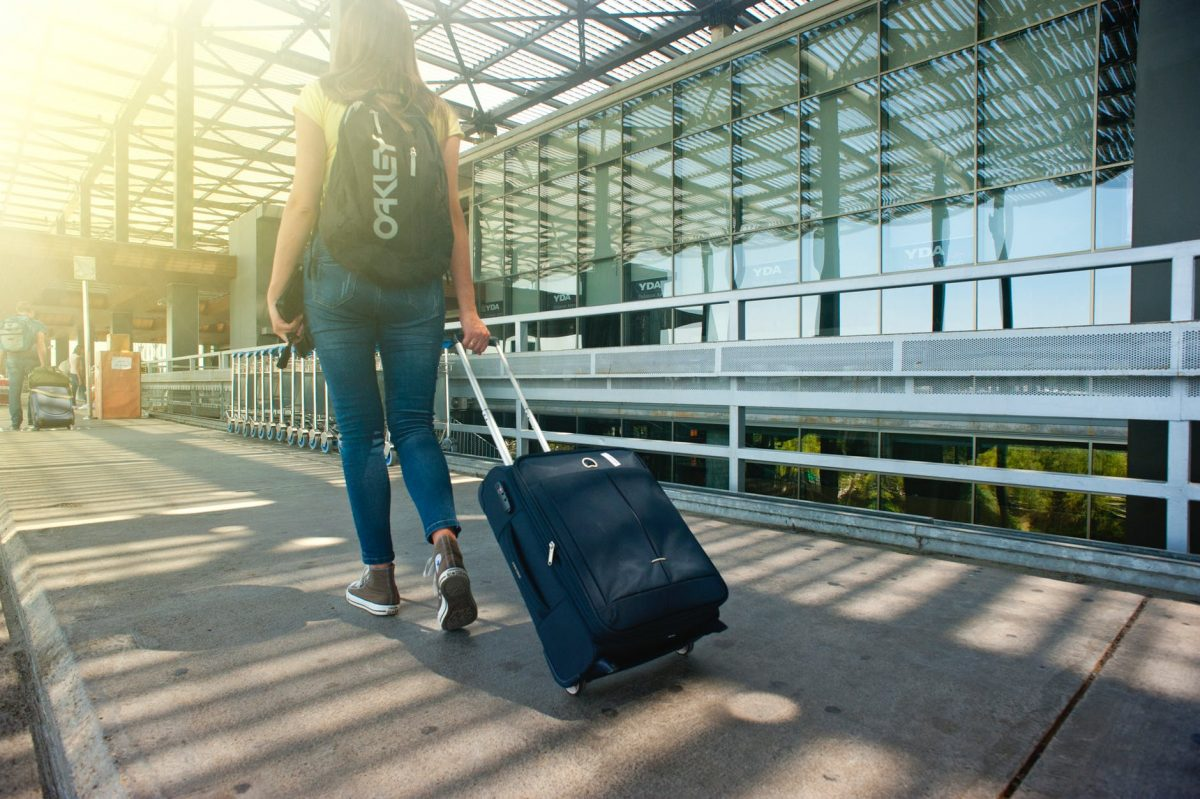Girl walking into an airport with luggage