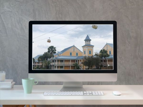 Computer with a picture of a Disney Resort on the computer monitor