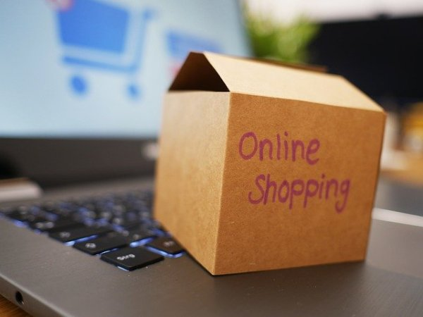 """A box labeled """"online shopping"""" sitting on a laptop"""