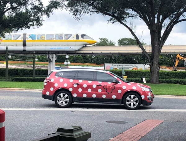 Disney's Minnie Van driving by as the monorail goes by in the background.