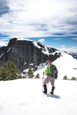 a man stands wearing snowshoes with Mount Heber in the background