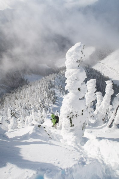 looking down on a man as he snowshoes up a steep hill, a mountain valley falls bellow