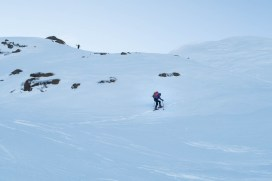 two figures hiking up snow covered slopes on Adder Mountain