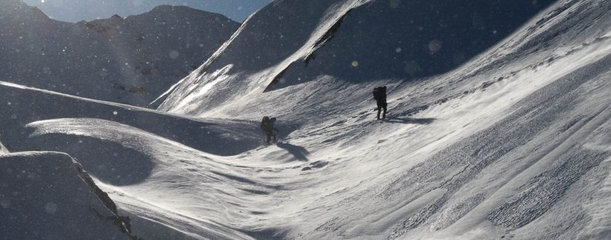 two figures walk into the wind on Adder Mountain