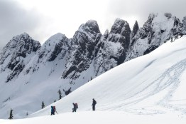3 figures stand with the peaks of the Mackenzie Range as the backdrop