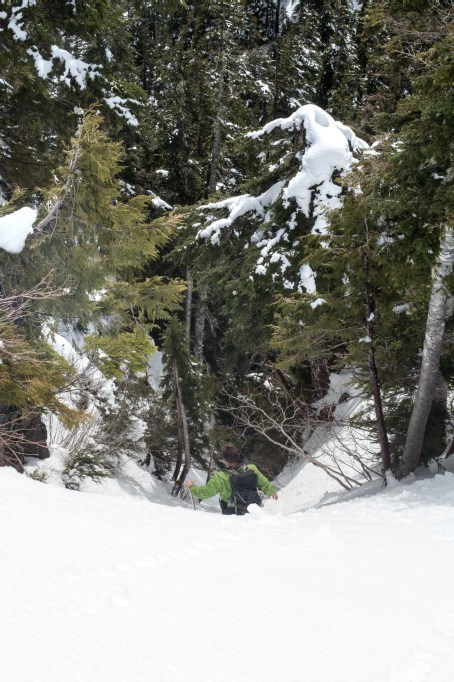 a man descending a snow-filled gully