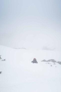 a woman ascending steep snow on Mount Adam