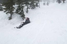 Colleen descending via a butt-slide on Mount Adam