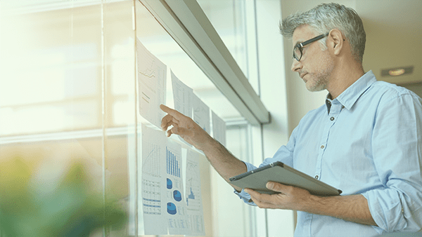 Image: Outcomes - Businessman analyzing results charts hanged on office window