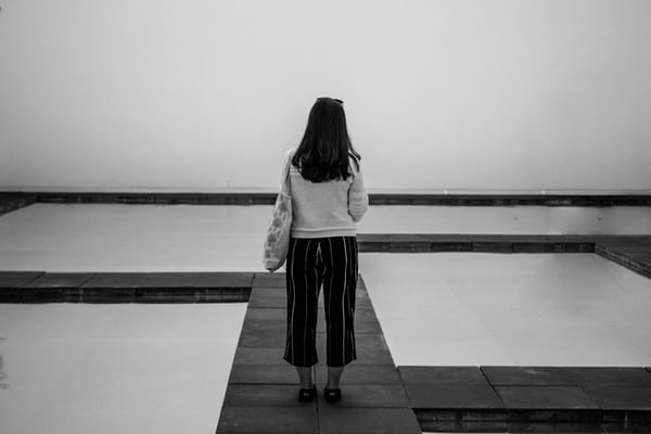 person standing alone between square pools of water