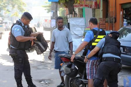 Policiais revistam um motociclista