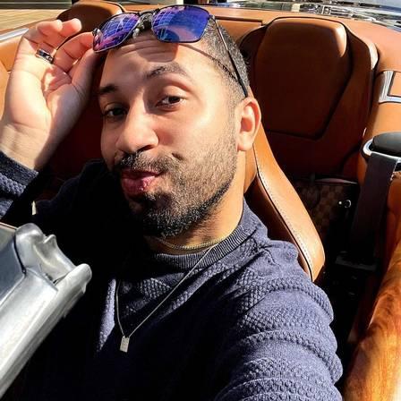 Gil poses in convertible car
