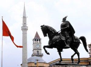 Koti, uskonto ja isänmaa. Albanian kotkalippu, Et'hem Beyn moskeija ja kansallissankari Skanderbegin patsas.