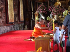 A monk blessing children with holy water.
