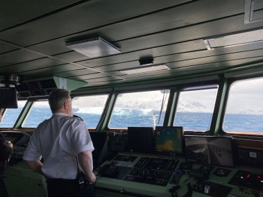 The ship's captain on bridge. There's a large iceberg not far from the ship.