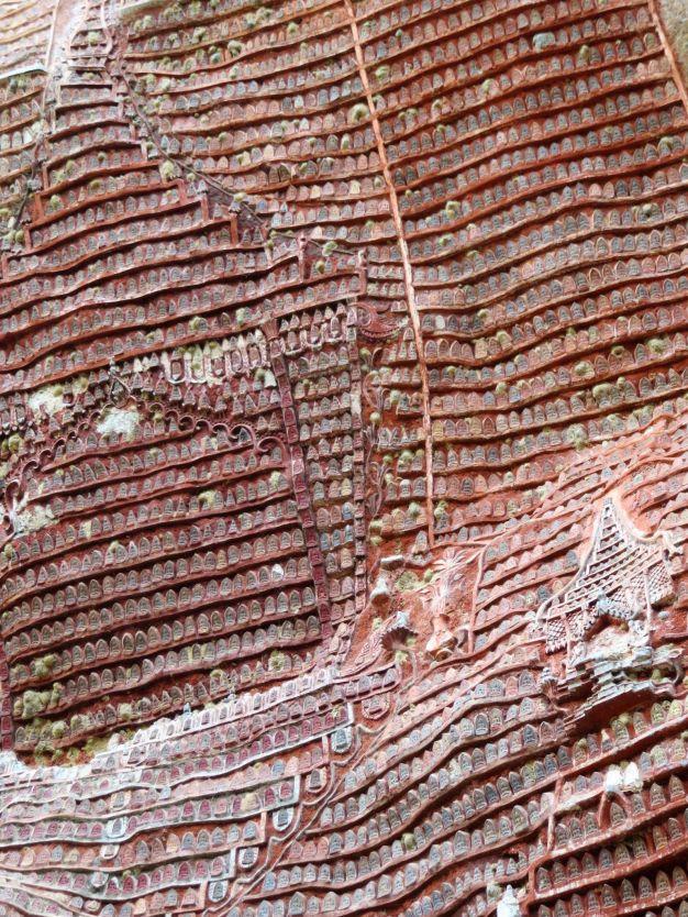 Budas emplastados en la pared de la roca en Kawgoon Cave