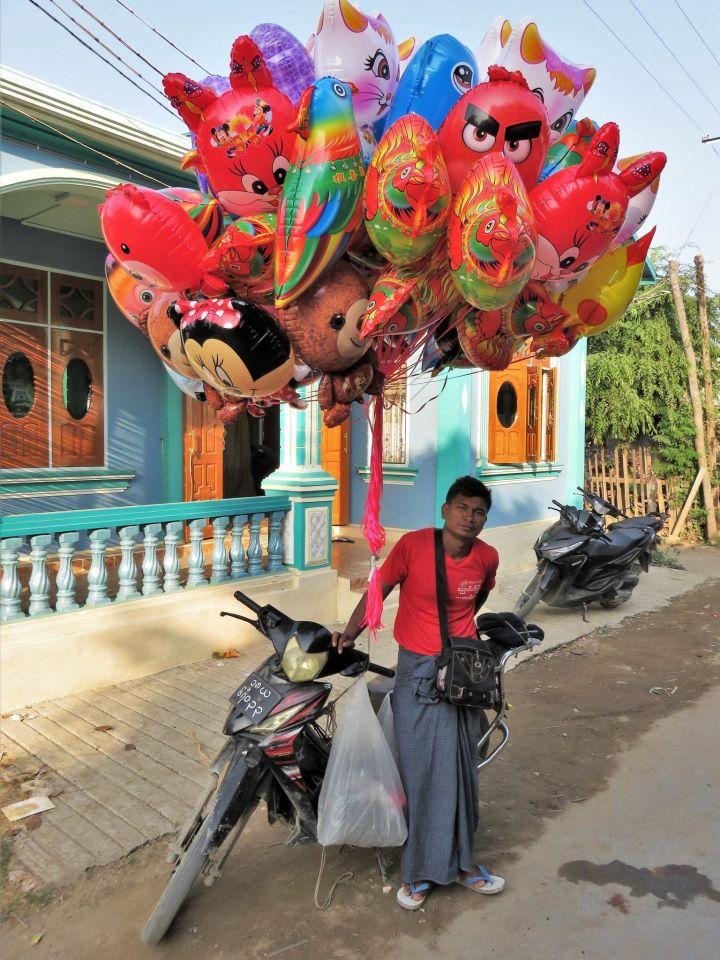Vendedor ambulante de globos en moto