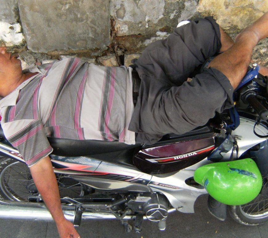 Hombre durmiendo sobre su moto