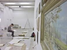 (63) Il est concentré sur une mise en place rigoureuse sur le mur le plus long, «Les Ponsées» sont numérotées, cataloguées, il s'active avec précision, le vernissage est dans deux jours...