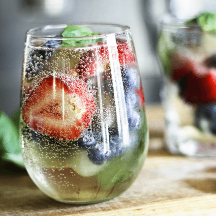 Sangria-by-the-glass makes it so you don't need to whip up a whole pitcher to enjoy Sangria! Sparkly, slightly sweet, berry-and-basil fresh!