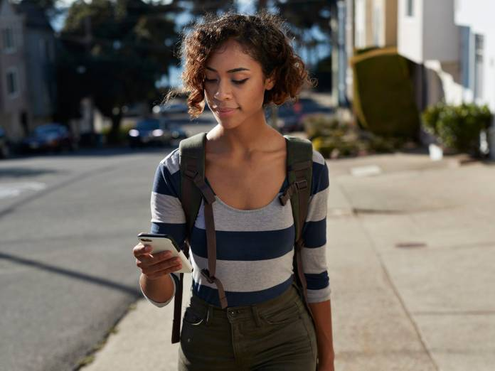A Gen Z woman walking down the sidewalk while looking at her phone