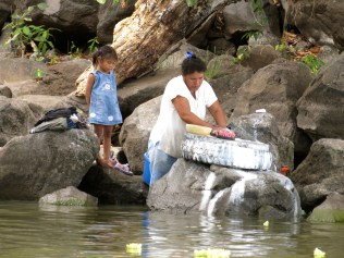 A local Nica woman does her washing in the water as her little girl looks on