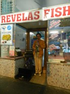 A busker takes shelter outside a Fish shop and performs for Long Street