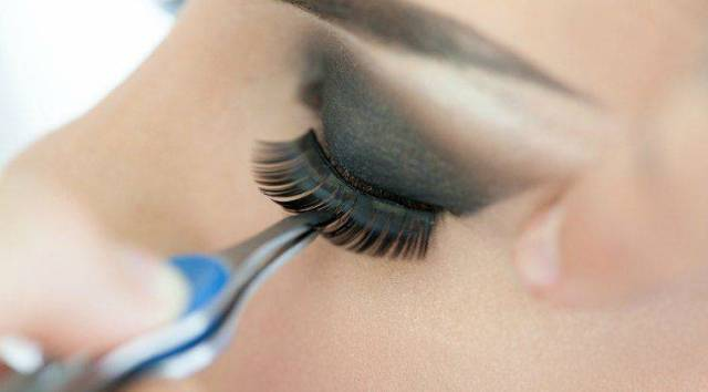 a model using a tweezer on her lash extensions