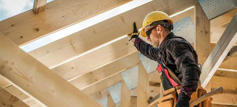 man in work protective gear with hammer in rafters