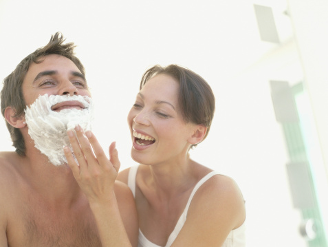 A woman helping a man shave