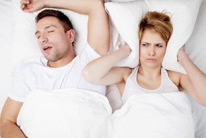Wife feeling annoyed while her husband snores loudly