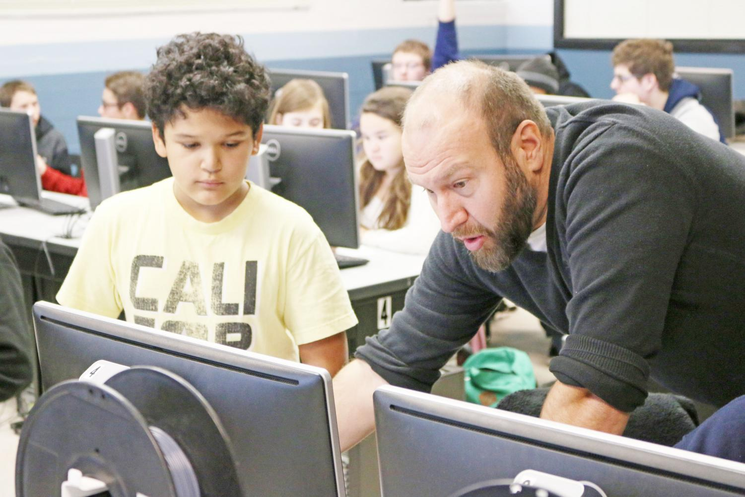 PLTW Engineering teacher John Fuller works with a student in his Intro to Engineering course last week. Fuller is unable to teach the third course in the current engineering track scheduled for next term due to improper credentialing. (NICK PROVENCAL/EYE OF THE TIGER)