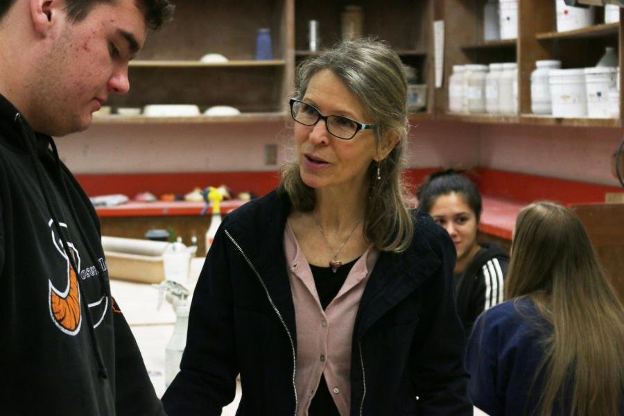 Ceramics teacher Joyce Henry works with students in class.